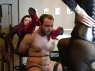 He sits still while two babes kick him in balls