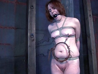 Bootylicious redhead loves getting punishment while bonded to a pole