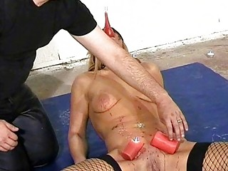 Busty blonde slave is punished with hot wax and ass-probing