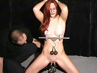 Submissive redhead gets her boobs and pussy punished with weights